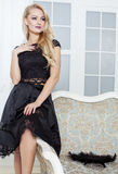 Stylish elegant blonde woman in beauty rich interior, wearing black dress smiling Stock Photography