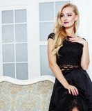 Stylish elegant blonde woman in beauty rich interior, wearing black dress smiling, lifestyle people concept royalty free stock photography