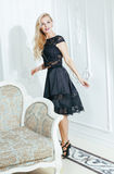 Stylish elegant blonde woman in beauty rich interior, wearing black dress smiling Stock Images