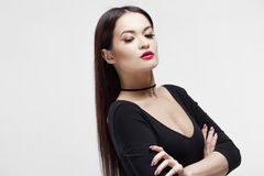 Stylish and elegant brunette in black on white background, portrait in Studio. Young woman with stylish laconic make-up and luxurious smooth hair stock photo