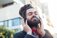 Stylish elegant dreadlocks businessman listening to music Royalty Free Stock Photos