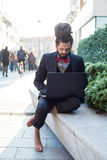 Stylish elegant dreadlocks businessman using notebook Stock Images