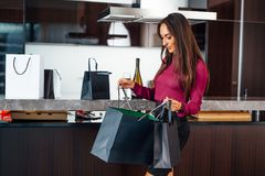 Stylish elegant lady at home after shopping peeping into the bags reviewing her purchases Stock Photos