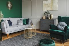 Stylish emerald green and grey living room interior design with abstract painting on the wall