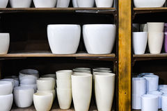 Stylish empty flower pots on wooden shelf indoor in shop. Many stylish gray brown and white empty flower pots on wooden shelf indoor in shop stock photos