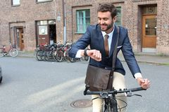 Stylish ethnic man riding a bicycle in the city.  Royalty Free Stock Images