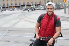 Stylish ethnic man riding a bicycle in the city with copy space.  Stock Photos