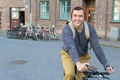 Stylish ethnic man riding a bicycle in the city.  Royalty Free Stock Image