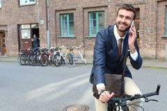 Stylish ethnic man riding a bicycle in the city.  Stock Photo