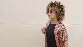 Stylish ethnic woman on street. Side view of modern young African American woman with voluminous curls wearing sunglasses and walking with backpack on street stock video