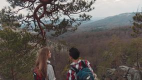 Stylish European backpackers reach the summit top, they observe amazing view of mountains and forest, smiling and. Holding their hands. Romantic atmosphere stock video