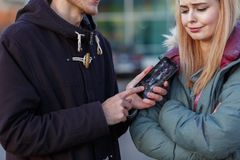 A guy shows with two hands a broken phone to a girl close-up on a blurred background royalty free stock photography