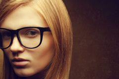 Stylish eyewear concept. Portrait of a young beautiful red-haired model (student) wearing trendy glasses and posing over golden b royalty free stock images