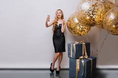 Stylish fair-haired girl with red lips making photo before birthday, using smartphone. Indoor portrait of stunning young. Women with long blonde hair posing royalty free stock photography