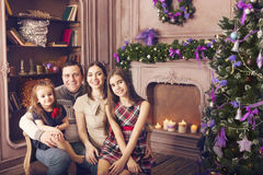 Stylish family celebrating christmas in room over christmas tree Royalty Free Stock Images