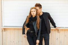 Stylish fashion beautiful couple in black jackets on the beach. Stylish fashion beautiful couple in black jackets on the beach stock images