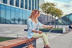 Stylish fashion blogger using the laptop for work while sitting outside on a bench against a skyscraper. Stock Photography
