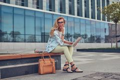 Stylish fashion blogger using the laptop for work while sitting outside on a bench against a skyscraper. Royalty Free Stock Photo