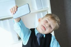 Stylish fashion business boy making selfie on mobile phone in office background. Boy playing boos stock images