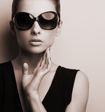 Stylish fashion female model in fashion sunglasses posing. Black Royalty Free Stock Images