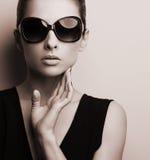 Stylish fashion female model in fashion sunglasses posing. Black royalty free stock images