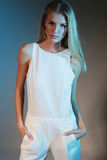 Stylish fashion photo of beautiful slim model in a white suit with straight blond hair Royalty Free Stock Images