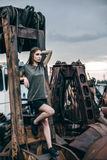 Stylish fashion portrait of trendy casual young model on a metal rusty detail royalty free stock image