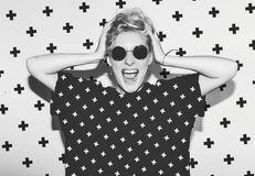 Stylish fashion sexy blonde bad crazy girl in a black t-shirt and rock sunglasses scream holding her head. Dangerous. Rocky emotional woman. Black and white Stock Photography