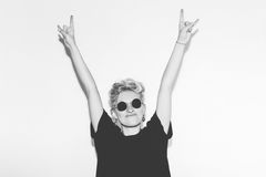 Stylish fashion sexy blonde bad girl in a black t-shirt and rock sunglasses. Dangerous rocky emotional woman giving the. Rock and Roll sign, devil horns gesture Royalty Free Stock Photo