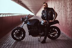 Stylish fashionable biker dressed in a black leather jacket with sunglasses holds a helmet sitting on his custom-made royalty free stock images