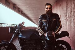 Stylish fashionable biker dressed in a black leather jacket with sunglasses holds a helmet sitting on his custom-made royalty free stock image