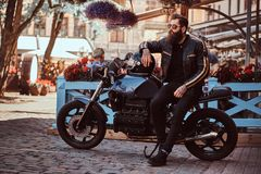 Stylish fashionable biker in sunglasses dressed in a black leather jacket, sitting on his custom-made retro motorcycle royalty free stock photo