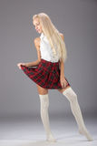 Stylish fashionable blonde woman in white shirt and plaid skirt Royalty Free Stock Photography