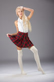 Stylish fashionable blonde woman in white shirt and plaid skirt Stock Photography