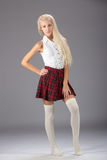 Stylish fashionable blonde woman in white shirt and plaid skirt Stock Photos