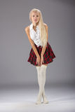Stylish fashionable blonde woman in white shirt and plaid skirt Stock Images