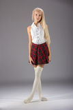 Stylish fashionable blonde woman in white shirt and plaid skirt Royalty Free Stock Image