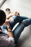 Stylish fashionable girl with a Cup of coffee and a green manicure in jeans. Fashion, care, beauty Stock Photos