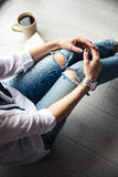 Stylish fashionable girl with a Cup of coffee and a green manicure in jeans. Fashion, care, beauty Stock Photography