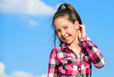 Stylish fashionable kid. Kids fashion concept. Kid girl checkered fashionable shirt posing sunny day blue sky background. Child cute girl long hair ponytail stock image