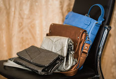 Stylish fashionable leather ladies purses lineup on black chair Royalty Free Stock Images
