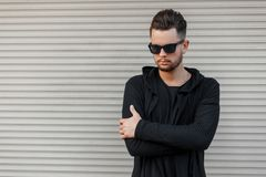 Stylish fashionable man in black sunglasses in a black hoody. Steals near a metal wall royalty free stock images