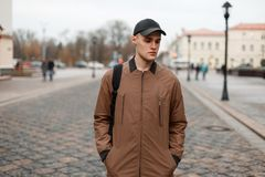 Stylish fashionable man in a vintage coat. And a cap with a black bag travel around the city Royalty Free Stock Image