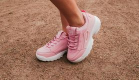 Stylish fashionable pink womens  leather shoes. womens legs with sneakers.  royalty free stock photography