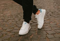 Stylish fashionable white womens leather shoes. Womens legs with sneaker. S royalty free stock images
