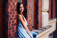 Stylish fashionable young brunette woman sits on a window sill near a brick wall and looks at the camera and smiles.... Royalty Free Stock Photo