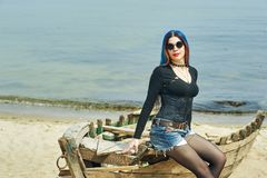 Stylish fashionable young girl on the beach . Girl sitting on an old boat Stock Photo