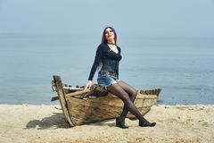 Stylish fashionable young girl on the beach . Girl sitting on an old boat Stock Images