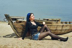 Stylish fashionable young girl on the beach . Girl sitting on an old boat Royalty Free Stock Image