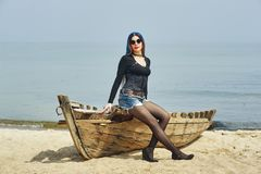 Stylish fashionable young girl on the beach . Girl sitting on an old boat Stock Image